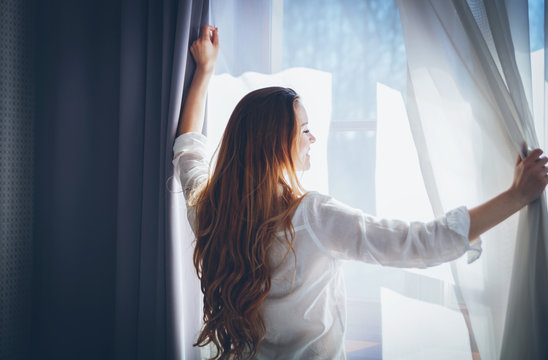 Pretty woman in modern apartment opening window curtains after wake up