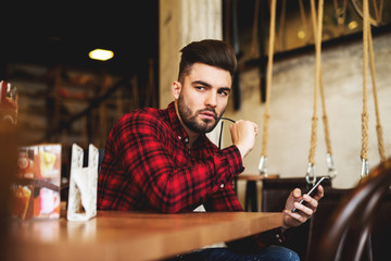 Hipster looking aside holding mobile phone.