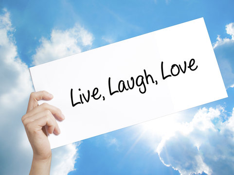 Live Laugh Love Sign on white paper. Man Hand Holding Paper with text. Isolated on sky background