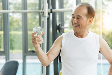 Asian senior man holding glass of water at a gym. Tired, thirstily. freshness.