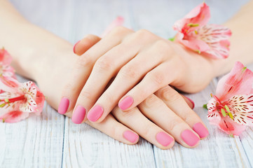 Woman hands with pink manicure on finger nails and delicate flowers
