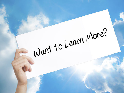 Want to Learn More? Sign on white paper. Man Hand Holding Paper with text. Isolated on sky background