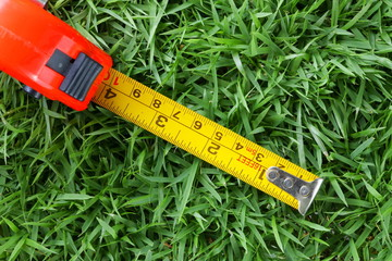 Old measurement tape cartridge put on the grass floor.
