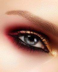 Closeup female eye with fashion bright make-up. Beautiful gold, red eyeshadow, glitter, black eyeliner. Shape Eyebrows
