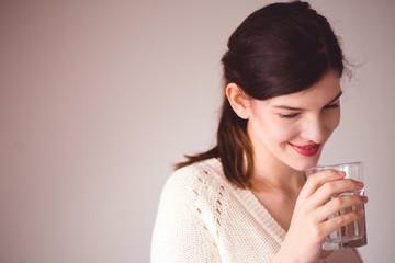 Junge Frau mit Wasserglas in der Hand