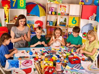 Plasticine modeling clay in children class. Teacher teaches kids play dough and mold from plasticine in kindergarten or preschool.