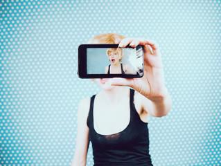 Chica joven y rubia sacándose un selfie con su teléfono móvil