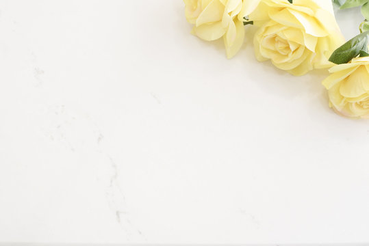 Yellow Roses over Marble Background, Border of Yellow Roses. Floral Frame with Flowers on wooden background. Styled marketing photography. Copy space. Wedding, gift card,  or mothers day background