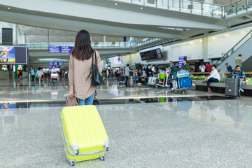 Back view of woman walking with luggage in Hong Kong international airport