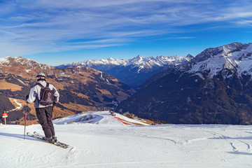 Man skier standing with his back on top of mountain ski resort in Mayrhofen, Austria, Zillertal valley. Sunny day. Picture from the ski resort in the Austrian Alps. Mountain skier looks into distance