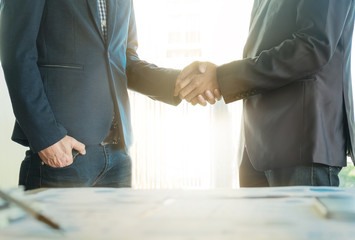 Two confident business man shaking hands during after a meeting in the office, success, dealing, greeting and partner concept.
