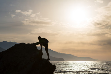 Climbing hiking silhouette in mountains and ocean