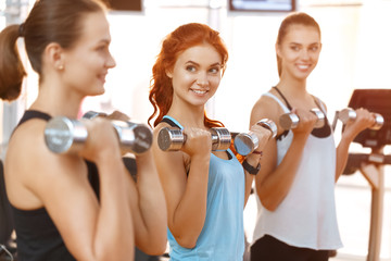 Three women exercising with dumbbells