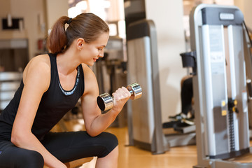 Sporty young female working out with dumbbells