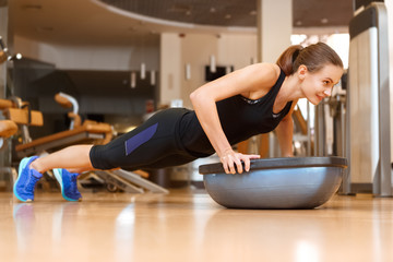 Young fitness woman exercising with bosu ball