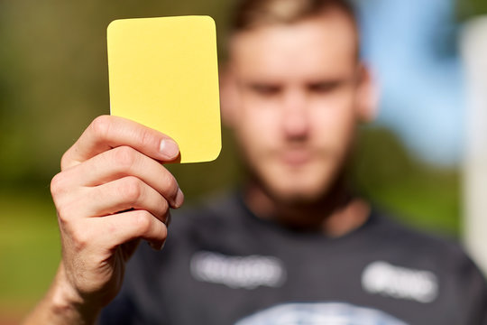 referee on football field showing yellow card