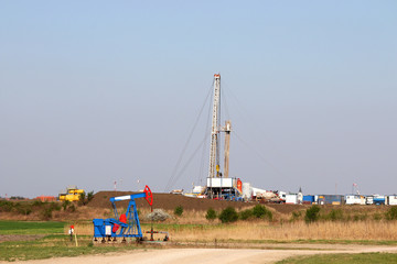 oilfield with pump jack and oil drilling rig