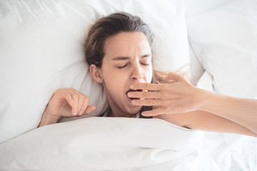 Donna sbadiglia a letto, assonnata
