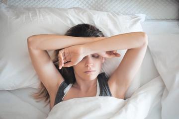 Donna a letto assonnata, sonno al mattino o stress