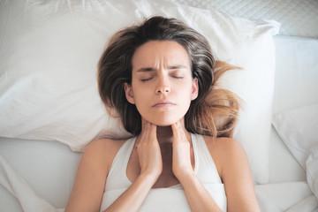 Donna con mal di gola, dolore a letto
