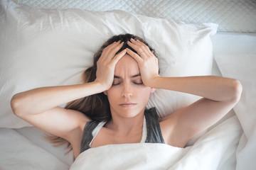 Donna con mal ti testa a letto, stressata