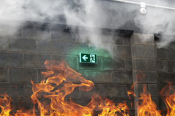 Emergency Fire Exit on the stone wall with fire and smoke