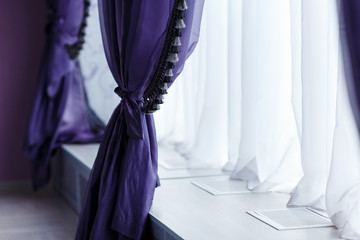 Purple curtains along window with a wide window sill. Day light, cool tones.
