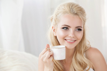 Beautiful young smiling woman sitting on white bed , drinking a cup of coffee