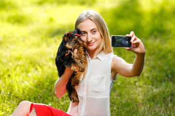Young beautiful woman taking selfie with her dog - small Yorkshi