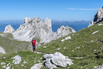 Funes Valley, Dolomites, South Tyrol, Italy. Hiker on the Alta Via Guenther Messner. In the background the peaks of Weisslahn