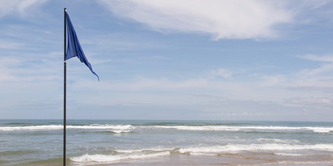 Flag blue and hoisted on the beach symbol of clean water ready for swimming