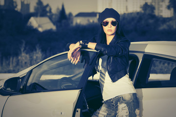 Young fashion woman in sunglasses standing next to her car