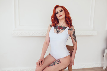Beautiful sexy girl with red hair and tattoo sitting on a chair in white body. Mock up.