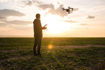 Man operating a drone with remote control. Dark silhouette against colorful sunset.