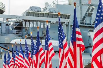 American flags with background Missouri Battleship in Pearl Harbor Honolulu Hawaii. Oahu island of United States. National historic patriotic monument.