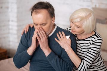 Elderly man sneezing near wife