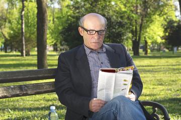 Senior newspaper reading in the park
