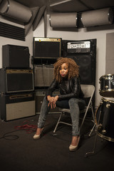 Young woman sitting on chair at recording studio