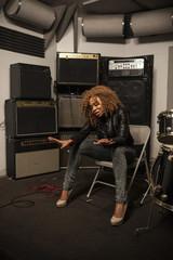 Young female singer singing at recording studio