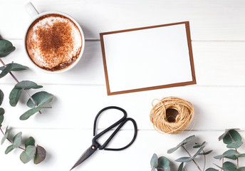 Blank paper, coffee and eucalyptus branches.