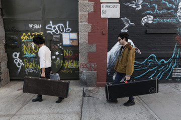 Young men carrying their guitar cases