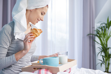 Breakfast to bed. The girl in the morning eats a croissant and listen music