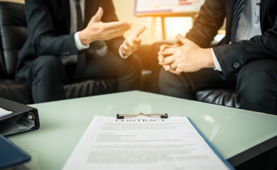 Close-up of business contract with pen at workplace on background of office workers interacting.