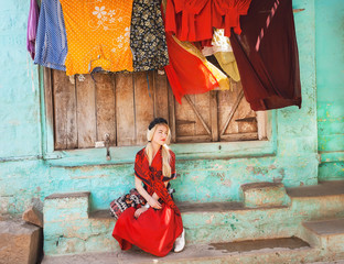 Young woman in red relaxing on the porch of traditional indian rural house with colorful clothes dries after washing.