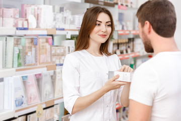 Professional pharmacist working with customers at the drugstore