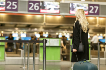 Cheerful young businesswoman walking with her suitcase through the airport