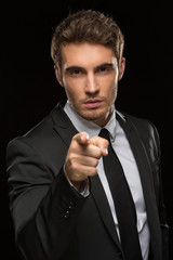 Young man in a suit pointing with his finger