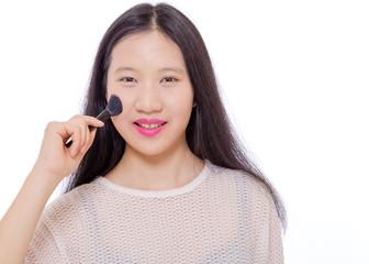 Teenage girl applying makeup with a brush