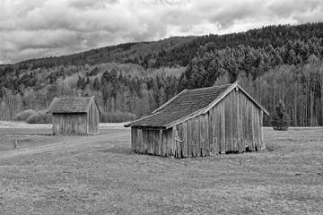 Alter Heustadl im Alpenvorland mit den bayrischen Bergen im Hintergrund, schwarzweiß, Bayern, Deutschland
