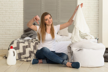 Upset girl holding dirty laundry and showing thumbs down.